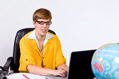 Female sitting behind a desk in bright, yellow jacket Stock Images