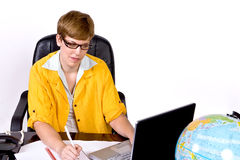Female sitting behind a desk in bright, yellow jacket. And glasses, writing something as she looks at a laptop computer Royalty Free Stock Images