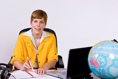 Female sitting behind a desk in bright, yellow jacket. Holding a pen between her fingers and looking forward Stock Images