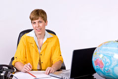 Female sitting behind a desk in bright, yellow jacket. Holding a pen between her fingers and looking forward Royalty Free Stock Photography