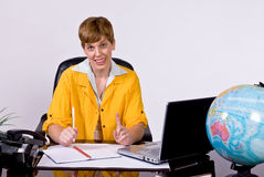 Female sitting behind a desk in bright, yellow jacket. Holding up a finger as if to say hold on one moment Stock Image