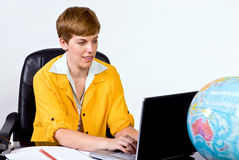 Female sitting behind a desk in bright, yellow jacket. Working on a laptop computer Stock Image