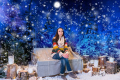 Female sitting on a bench or a swing in the evening in a snow-co Stock Photo