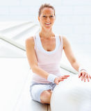 Female sitting besides a fitness ball Royalty Free Stock Photo