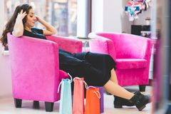 Female sitting on a chair surrounded by shopping bags Royalty Free Stock Image