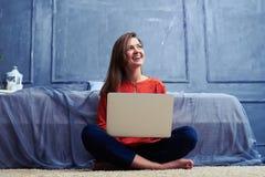 Female sitting cross-legged with laptop looking upward Stock Photography