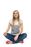 Female sitting with crossed legs on the floor Stock Images