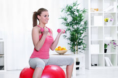Female sitting on a fitness ball with dumbbells Stock Photography