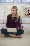 Female sitting on floor with cell phone and laptop Stock Photos