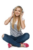 Female sitting on floor enjoying music in headphones Royalty Free Stock Images