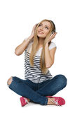 Female sitting on floor enjoying music in headphones Royalty Free Stock Image
