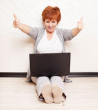 Female sitting on floor with laptop Stock Photo