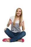 Female sitting on floor showing thumb up signs. Happy young female sitting on floor showing thumb up signs, isolated on white background stock photography