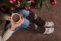 Female sitting on floor and warmers leg socket and with cup of coffee in hand and next to Christmas tree. Young female legs with warmers on floor carpet holding royalty free stock photography