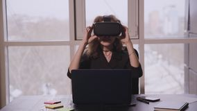 Female sitting front of laptop screen in office room. American woman having fun with new futuristic cyber game by vr glasses stock video footage