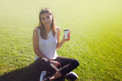 Female sitting on the grass drinking coffee in a cardboard Cup Stock Photos
