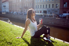 Female sitting on the grass drinking coffee in a cardboard Cup Royalty Free Stock Images