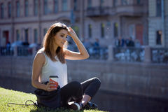 Female sitting on the grass drinking coffee in a cardboard Cup Stock Photography