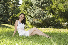 Female sitting on grass field at the park Stock Photo