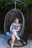 Female sitting on hanging chair. Female sitting on vintage hanging chair in the garden stock photos