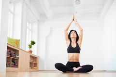 Woman sitting and looking up with hands up. Meditating doing breathing yoga bandhas. Health and wellness. Low angle view. Female sitting and looking up with stock images