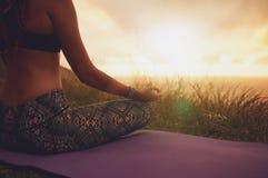 Female sitting in lotus yoga pose on exercise mat. Close up shot of female sitting in lotus yoga pose on exercise mat, with focus on hands. Fitness female Stock Photo
