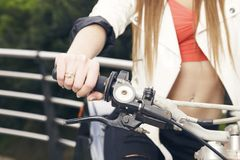 Female sitting on a motorcycle, hand on grip, outdoors. Female sitting on a motorcycle, hand on grip, outdoors, ready to go. No face Royalty Free Stock Photo