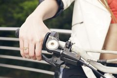 Female sitting on a motorcycle, hand on grip, outdoors. Royalty Free Stock Images