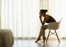 Female sitting near window in thoughtful pose Stock Photography