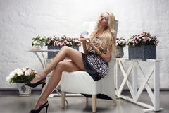 Female sitting posing holding tea cup Royalty Free Stock Image