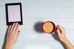 Female sitting, reading e-book and hands hold cup of coffee Royalty Free Stock Photo