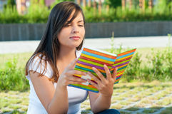 Female sitting and reading from journal or agenda Stock Photos