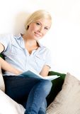 Female sitting on the sofa reads a book Royalty Free Stock Photos