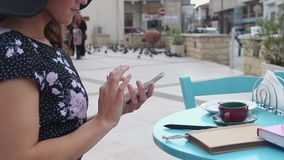 Female sitting at street cafe table, using smartphone, typing message, scrolling. Stock footage stock video