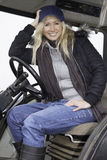 Female sitting in a tractor. Happy female sitting in a tractor Stock Images