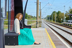 Female sitting and waiting train on the platform Stock Photography