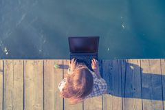 Female sitting on wooden dock and working on laptop. stock images