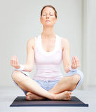 Female sitting on yoga mat meditating Royalty Free Stock Photo