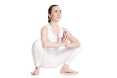 Female sitting in yoga squat. Sporty smiling beautiful young woman in white sportswear sitting in squat, Garland Pose, Malasana with hands in Namaste, studio Royalty Free Stock Images