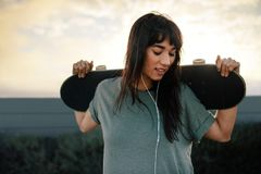 Female skateboarder standing outdoors with her skateboard. Female skateboarder standing outdoors holding her skateboard. Beautiful young woman with skating board Royalty Free Stock Images