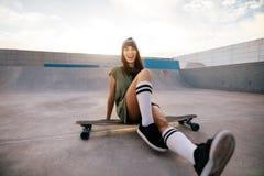Female skater having fun at skate park. Smiling woman skateboarder sitting on her long board. Female skater having fun at skate park Royalty Free Stock Photo