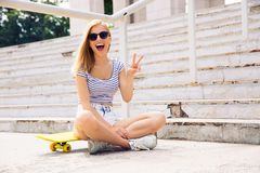 Female skater showing two fingers sign o Stock Photo