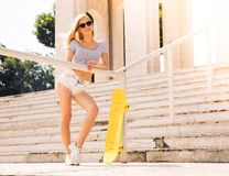 Female skater in sunglasses standing outdoors Royalty Free Stock Image