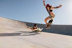 Female skaters doing stunts at skate park. Two women doing stunts on skateboards at skate park. Female friends practising skateboarding outdoors Stock Photos