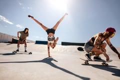Female skaters enjoying at skate park. Woman doing flip with female friends skateboarding at skate park. Group of female enjoying at skate park Royalty Free Stock Photo