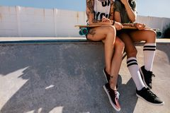 Female skaters sitting together on skating ramp. Legs of two female skaters sitting together on skating ramp at skate park. Cropped shot of women sitting on ramp Royalty Free Stock Images