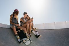 Female skaters using smart phone at skate park. Group of female friends sitting on ramp at skate park and looking at mobile phone. Three women skaters using Stock Image