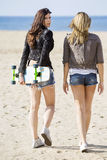 Female Skaters Walking At Beach stock photo