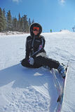 Female skier. Happy young mountain skier resting on the slope smiling Royalty Free Stock Image