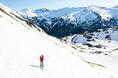 Female skier ascending a mountain slope. Royalty Free Stock Photo